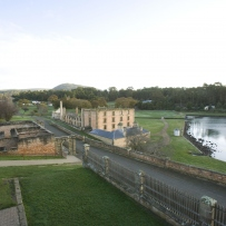 Long shot of historic convict site featuring derelict institutional buildings and a roadway, with paddocks and bushland and the edge of a waterway.