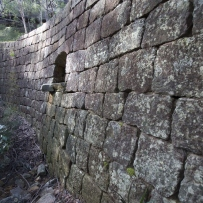 Large stone retaining wall, covered in moss, made of sandstone blocks, with a drainage channel visible to allow water to pass under the road.