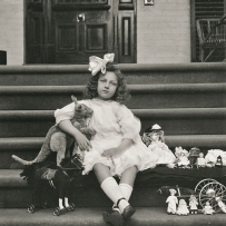 Girl with large white bow in her hair sits on steps with front door in the background. She is surrounded by toys including dolls and holds a toy kangaroo under her arm.