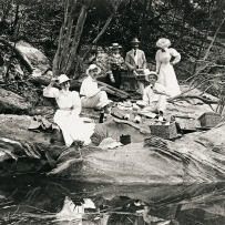 Group of people sit on rocks beside a quite stream after a picnic