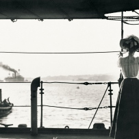 Woman stands with her back to the camera viewing departing ship through a telescope.