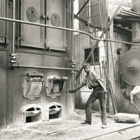 Young man opens a hopper at the base of a large cast iron boiler. His face blackened with soot is turned to the camera.