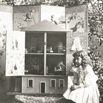 Small girl sits beside a large dolls house, its doors open revealing wallpapered rooms and toys inside.