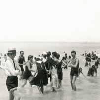 A group of young people frolic in the shallow water at the beach. A mix of long swim suits and dresses are worn with a boy in the foreground wading with rolled up trousers.