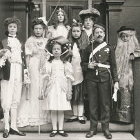 Group of children stand on the steps of a house dressed in costume for a play.