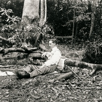 Man rest on the ground, propped on a fallen tree smoking a cigarette. The dense rainforest can be seen in the background.