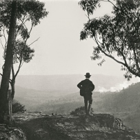 Man Stands on the edge an escarpment looking out over an extensive view of the a wooded valley below.