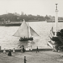 People gather at the edge of the harbour. A small boat with white sails is in the middle of the image with the Botanic Gardens and Fort Macquarie at Bennelong Point in the background.