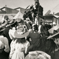 a panoramic image of crowds at a side show. Young girl with long hair and hat is in the foreground. An unclear attraction is on a stage is in the background.