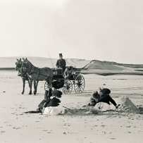 On an outing at Bondi, dressed for winter in stockings, shoes, hats and coats, the Allen children build sandcastles with their mother, Ethel, while the coachman, Jacob, waits in the horse-drawn cart.