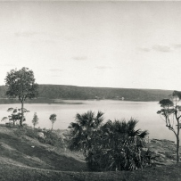 Panoramic image of the soft hills, lawn and view over the Port Hacking with a lady in white dress sitting in the foreground.