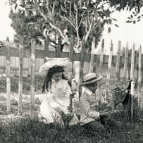 Two children, a girl with long hair and large white hat and boy with straw boater each hold a baby emu.