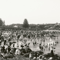 Crowds cover the rocks and sand at Coogee Beach on a hot day.