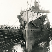 Large ship sits in a dockyard.