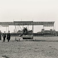 Figures gather around an early plane, the boxkite in a field.