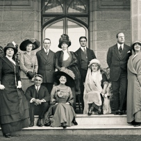 Group gather on the steps outside imposing sandstone house. All formally attired the men in suits, the women in close fitting dresses and elaborate hats.