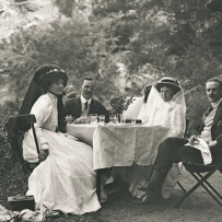 Four people sit outside gathered around a small table with white table cloth, surrounded by trees.