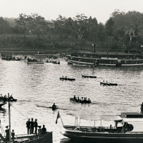 View of river with a number of row boats and larger pleasure craft lining the banks of the river watching a rowing race.