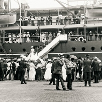 A crowd farewells a large ship at a dock. Two men walk in the foreground wearing suits, waistcoats and hats.