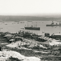 Black and white photograph showing view of harbour with ships with rocks in foreground.