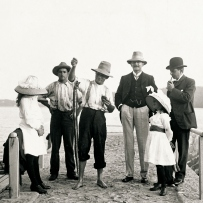 Group of children and adults gather on a jetty. Man in centre holds large eel caught on a fishing hook.
