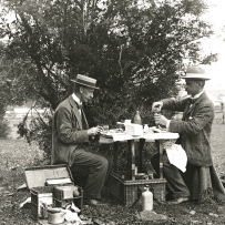 Two men sit at a well equiped picnic table with white table cloth. The table folding out of the picnic basket.  One pours a drink and the other places fodd on the table.