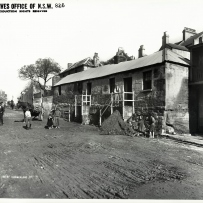 Photograph of a row of small cottages lining a dirt street. Children are shown standing on the street.