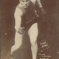 Boxer Tommy Burns posing in a photographic studio posing in an attacking boxing position with his boxing shorts, singlet and gloves