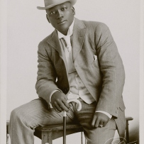 Boxer Johnson sits on a table wearing a brown suit and hat, holding a cane.