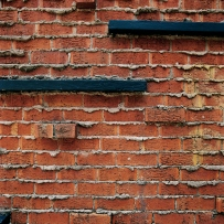 This is a detail photograph of a wall of red bricks with excess mortar applied, creating the appearance it is oozing out between the bricks