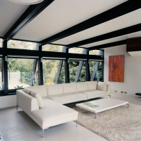 This is a photograph of a white sofa inside a white room with large windows behind and dark grey timber ceiling beams meeting with the matching window frames