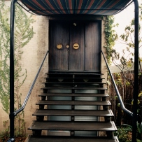 This is a colour photograph of open shallow timber staircase leading to a large timber door with a canopy covering the stairs and doorway