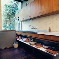 This is a photograph of a kitchen bench running along one wall with an open shelf below stacked with crockery. Timber cupboards are above and at one end is a window.