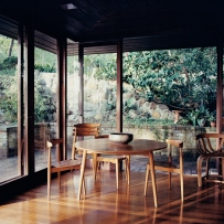 This is a photograph of a timber floored room open with large glass sheets on two walls and a timber dining table and chairs