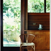 This is a photograph of a specially designed timber chair sitting in front of a timber cupboard and glass door