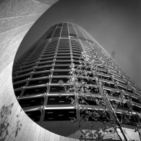 This is a black and white photograph of a tower building taken form below showing a sweeping curved wall at the base