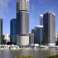 This is a colour photograph of an office tower with a wide river in the foreground