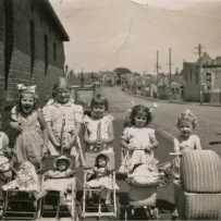 This is a black and white photograph of six young girls and one boy standing in a line in the street with dolly prams and tricycles