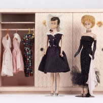 This is a colour photograph of three barbie dolls in various costumes standing in front of a 1950s style pink miniature wardrobe