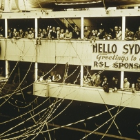 Sepia photograph of people waving from a ship.