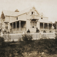 Black and white photograph of house exterior with people standing in front.