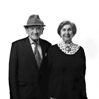 Black and white photo of elderly couple smiling at the camera. The man wears a black suite with pork pie hat and the lady wears a black jumper under a polka-dot shirt