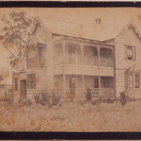 Photograph of exterior of house with three figures visible.