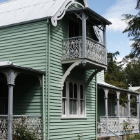 Exterior view of Meroogal, a two story green house. The sun is shining and the gardens look lush.