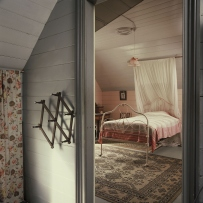 View of a bedroom with an iron bed with a mosquito net. The room has pink lining boards, a pink lamp shade and rugs