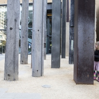 Children run beneath the tall poles of timber and steel that make up the edge of the trees sculpture