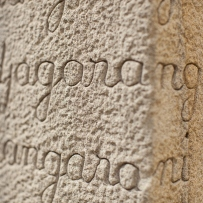 Closeup of sandstone carved with Gadigal words.