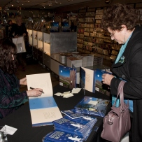 Jeannie Baker signing copies of book for guest