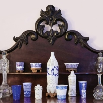 Set of blue and white patterned objects on dark timber dresser.