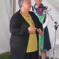 Two women on stage, one speaking into microphone.